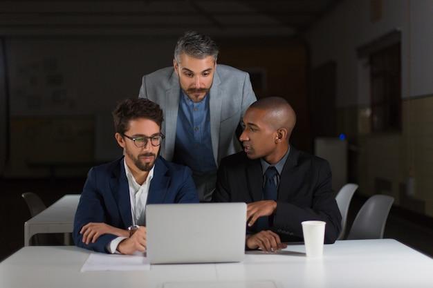Geschäftskollegen, die laptop im dunklen büro verwenden Kostenlose Fotos