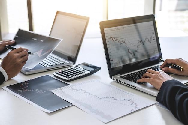 Geschäftskollegen, die mit computer arbeiten, börse besprechen und analysieren Premium Fotos