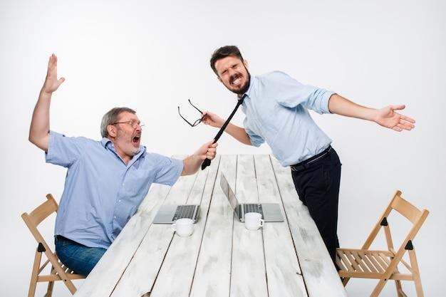 Geschäftskonflikt. die beiden männer drückten negativität aus, während ein mann die krawatte ihrer gegnerin packte Kostenlose Fotos
