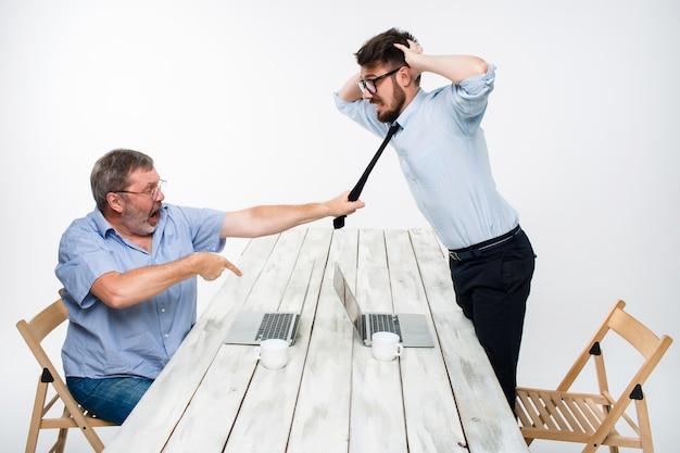 Geschäftskonflikt. zwei männer, die negativität ausdrücken, während ein mann die krawatte ihres gegners packt Kostenlose Fotos