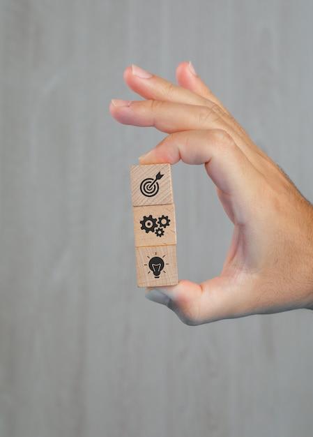 Geschäftskonzept auf grauer tischseitenansicht. hand hält holzwürfel mit ikonen. Kostenlose Fotos
