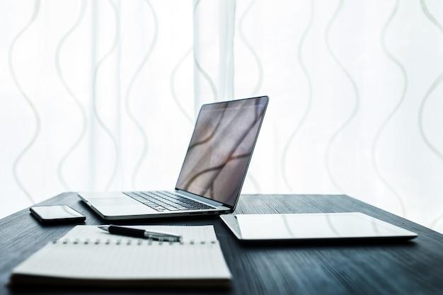 Geschäftskonzept, büroarbeitsplatz mit laptop auf hölzerner tabelle gegen die fenster Premium Fotos