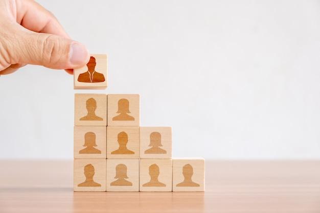 Geschäftskonzept des personal- und talentmanagements und der einstellung. hand von männern, die hölzernen würfelblock auf spitzentreppenhaus setzen Premium Fotos