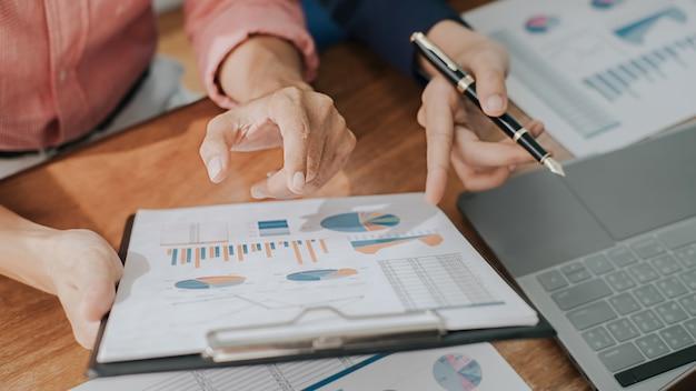 Geschäftskonzept. geschäftsleute diskutieren die diagramme und grafiken, die die ergebnisse ihrer erfolgreichen teamarbeit zeigen. Premium Fotos