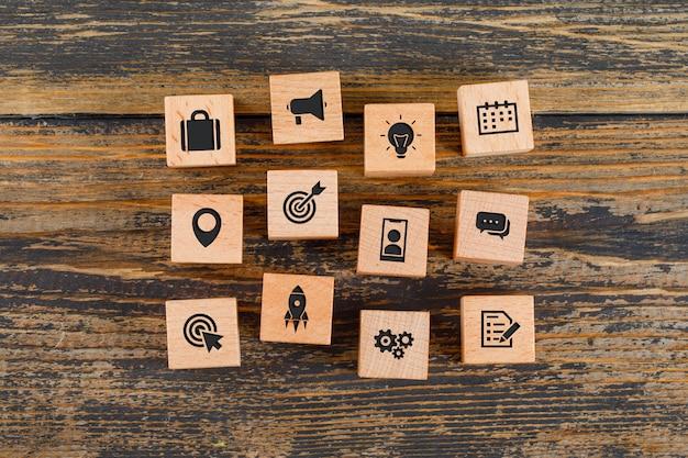 Geschäftskonzept mit ikonen auf holzwürfeln auf holztisch flach legen. Kostenlose Fotos
