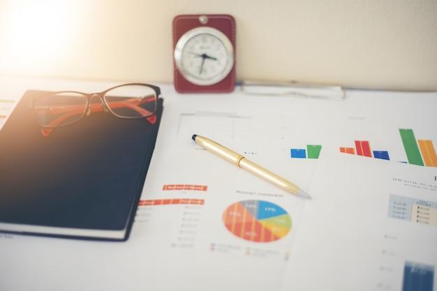 Geschäftskonzept von bürofunktions- und -analysegraphiken und -uhr auf tabelle Premium Fotos