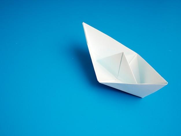 Geschäftskonzeptorigami weißes bootspapier minimal auf blauem hintergrund Premium Fotos