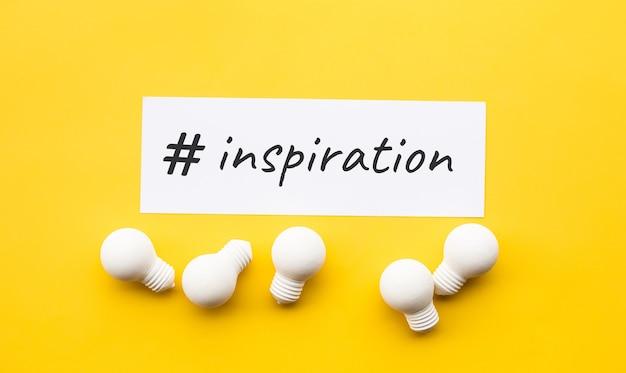 Geschäftskreativität mit inspirationstext und glühbirne auf gelbem hintergrund Premium Fotos