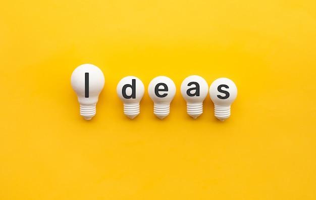 Geschäftskreativität und teamkonzepte mit glühbirne auf gelbem hintergrund Premium Fotos
