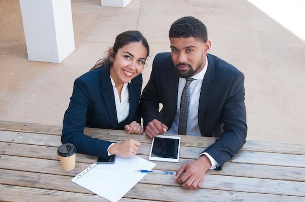 Geschäftsleute am schreibtisch mit tablette, dokument und getränk Kostenlose Fotos