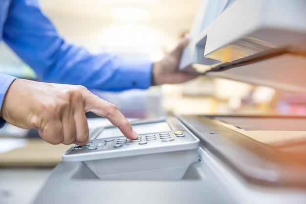 Geschäftsleute benutzen fotokopierer und scannen dokumente in office. Premium Fotos