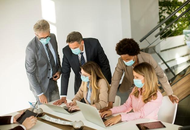 Geschäftsleute der gruppe treffen sich und arbeiten im büro und tragen als schutz masken Premium Fotos