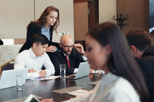 Geschäftsleute, die am konferenztische zusammenarbeiten Premium Fotos