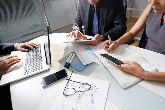 Geschäftsleute, die am schreibtisch arbeitet an projekt sitzen Kostenlose Fotos