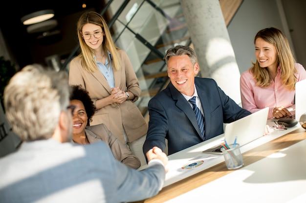 Geschäftsleute, die am schreibtisch im büro händeschütteln Premium Fotos