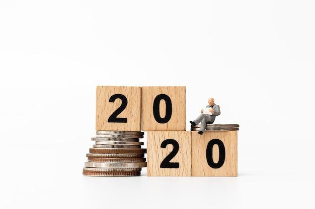 Geschäftsleute, die auf holzklotz nr. 2020 sitzen Premium Fotos