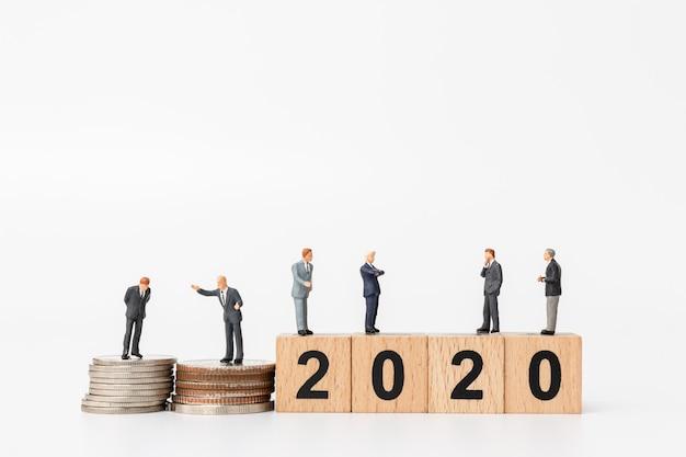 Geschäftsleute, die auf holzklotz nr. 2020 stehen Premium Fotos