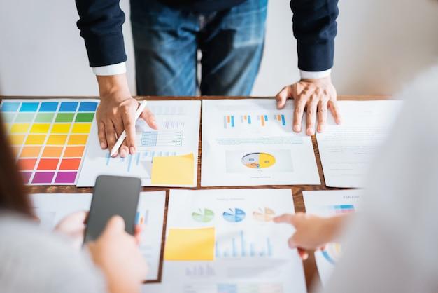 Geschäftsleute, die das team arbeitet an hölzernem schreibtisch- und handmann zeigt auf finanzdokumente im büro treffen. strategie für erfolgreiche besprechungsarbeitsplätze. Premium Fotos