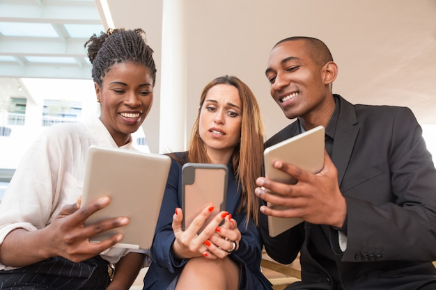Geschäftsleute, die dem verwirrten kollegen video oder fotos zeigen Kostenlose Fotos