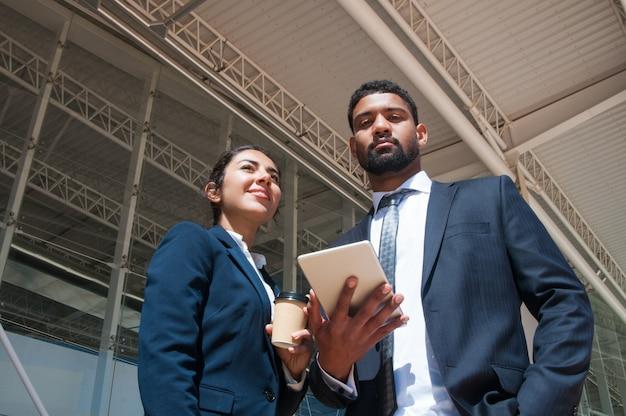 Geschäftsleute, die draußen tablette und getränk aufwerfen, halten Kostenlose Fotos