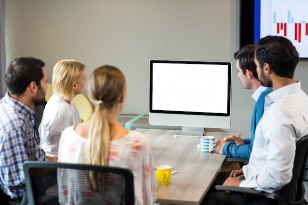 Geschäftsleute, die einen bildschirm während einer videokonferenz betrachten Premium Fotos