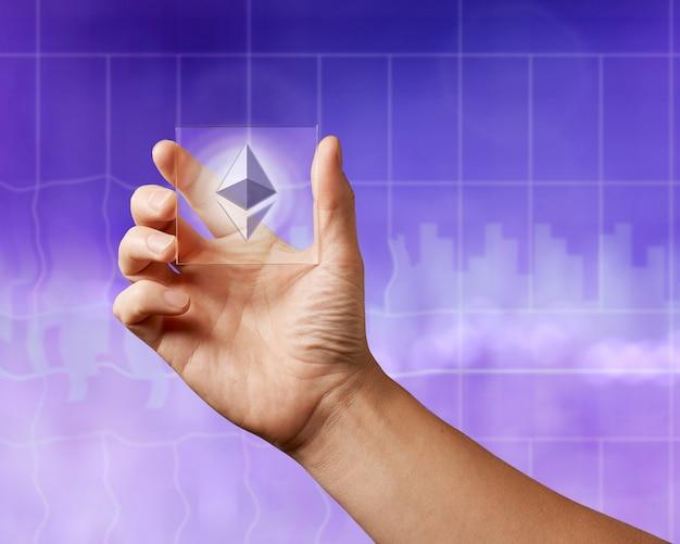 Geschäftsleute, die einen transparenten bildschirm mit einer ikone von etereum auf dem ultravioletten hintergrund der stadt halten. business, blockchain-technologie. Premium Fotos