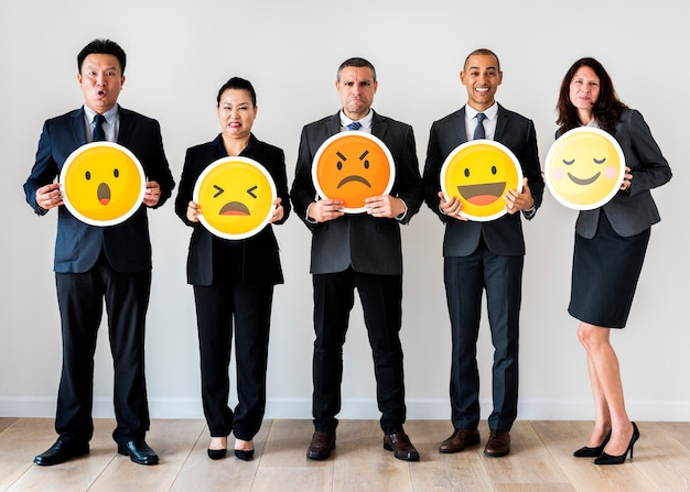 Geschäftsleute, die emoji ikonen stehen und halten Premium Fotos