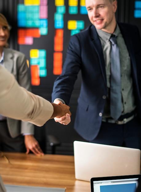 Geschäftsleute, die hände in einem konferenzzimmer rütteln Kostenlose Fotos