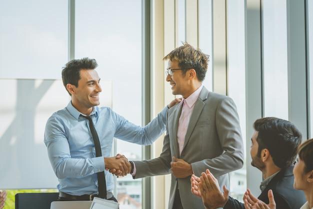 Geschäftsleute, die handglückwünsche rütteln, um erfolg zu bearbeiten Premium Fotos