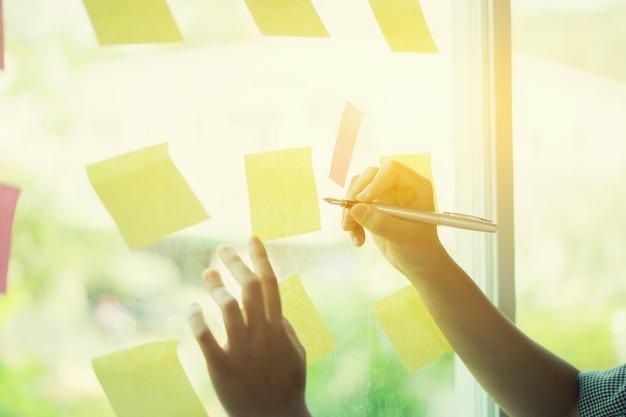 Geschäftsleute, die im büro sich treffen und post-itanmerkungen verwenden, um idee zu teilen Premium Fotos