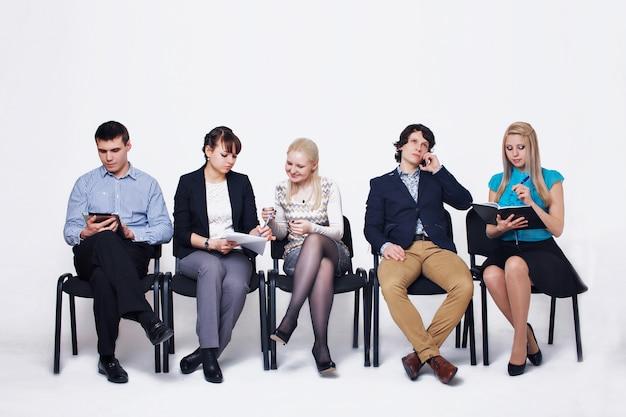Geschäftsleute, die in die warteschlange sitzt in der reihe hält smartphones und lebensläufe, personalwesen, beschäftigung und einstellungskonzept warten Premium Fotos
