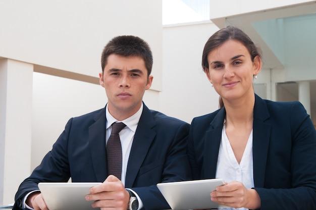 Geschäftsleute, die kamera betrachten und tabletten am schreibtisch halten Kostenlose Fotos