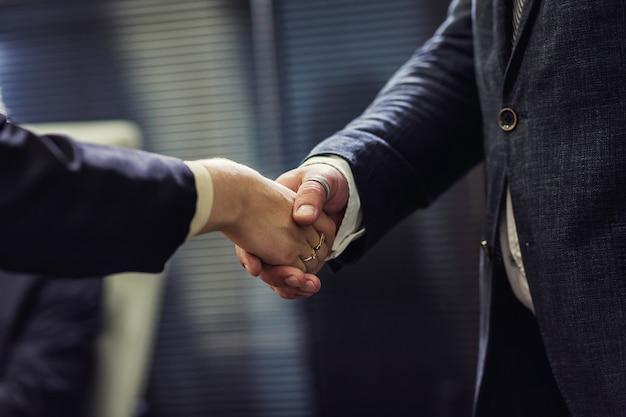 Geschäftsleute, die sich nach abschluss eines meetings als vereinbarung die hand geben Premium Fotos