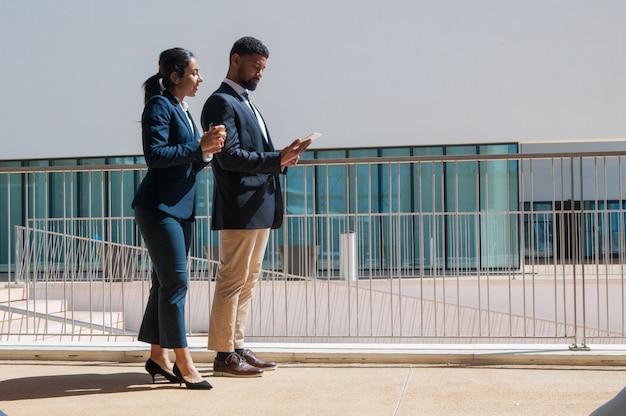 Geschäftsleute, die tablette verwenden und draußen stehen Kostenlose Fotos