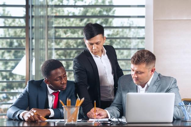 Geschäftsleute, die um einen sitzungssaaltisch sich treffen, der strategie bespricht Premium Fotos