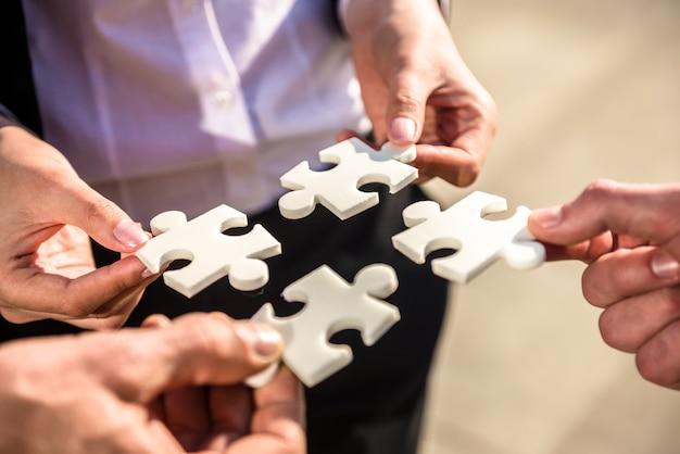 Geschäftsleute, die vier puzzleteile setzen möchten. Premium Fotos