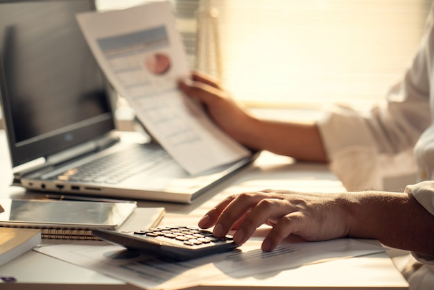 Geschäftsleute, die zinsen, steuern und gewinne berechnen, um in immobilien und den kauf von eigenheimen zu investieren Premium Fotos