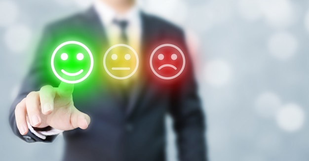 Geschäftsleute entscheiden sich dafür, glückliche symbole zu bewerten. umfrageerlebnis für kundenservice und geschäftszufriedenheit Premium Fotos