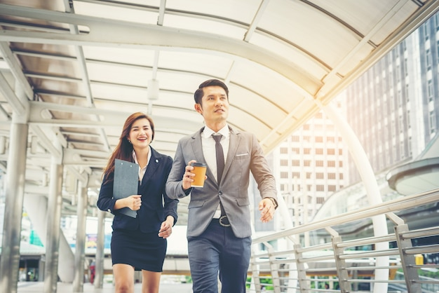 Geschäftsleute gehen durch passage büro. lächelnd zueinander. Kostenlose Fotos