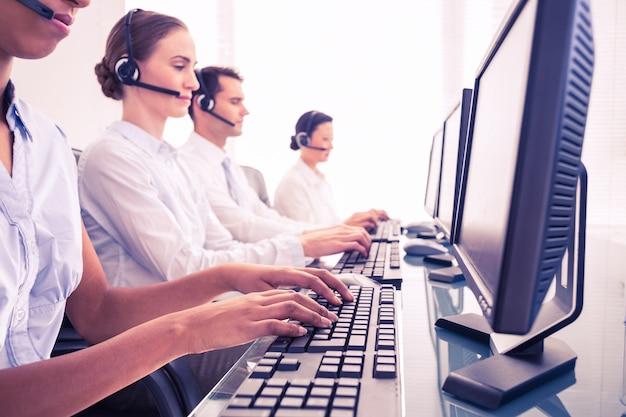 Geschäftsleute mit kopfhörern unter verwendung von computern Premium Fotos