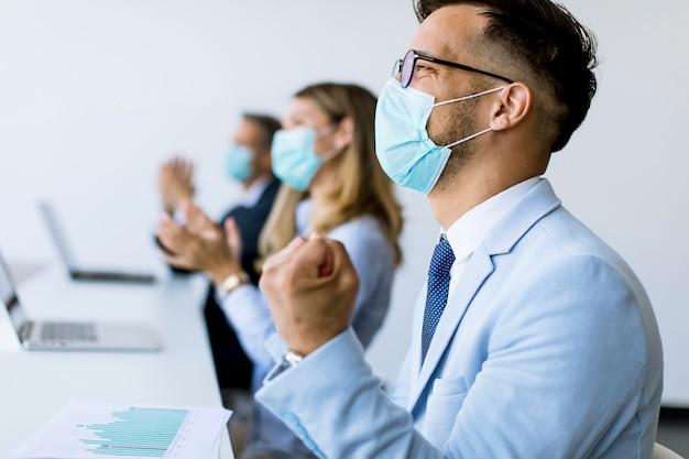 Geschäftsleute mit schutzmasken klatschen nach erfolgreichem geschäftstreffen im modernen büro in die hände Premium Fotos