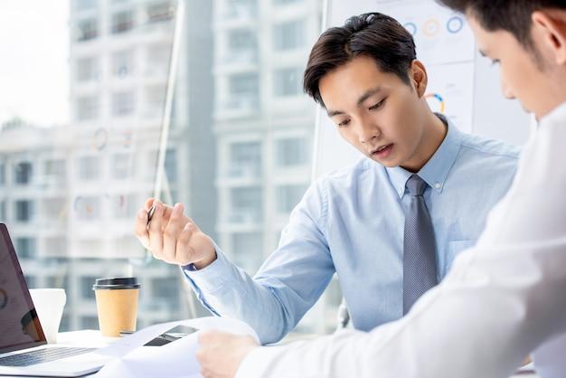 Geschäftsmänner, die dokumente am konferenzzimmer im modernen büro besprechen Premium Fotos