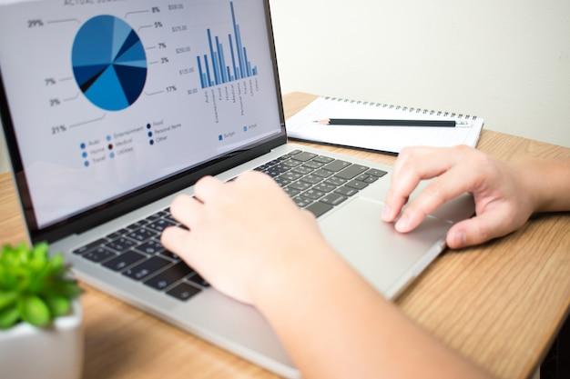 Geschäftsmänner, die mit finanzdiagrammen auf laptops am schreibtisch arbeiten. Premium Fotos