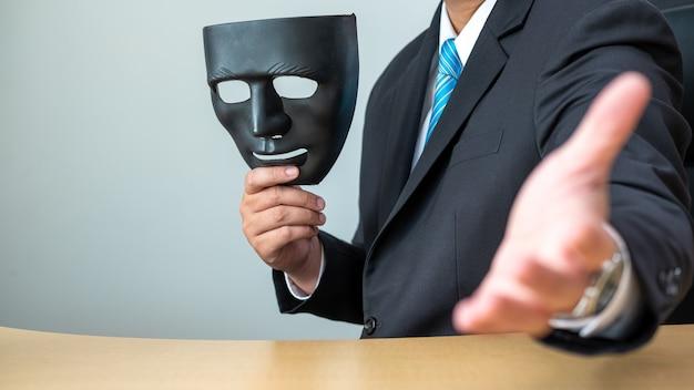 Geschäftsmänner, die schwarze maske und händedruck am schreibtisch halten Premium Fotos