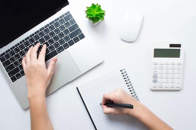 Geschäftsmänner machen sich notizen und benutzen laptops auf einer weißen tabelle. buchhaltungskonzept, draufsicht. Premium Fotos