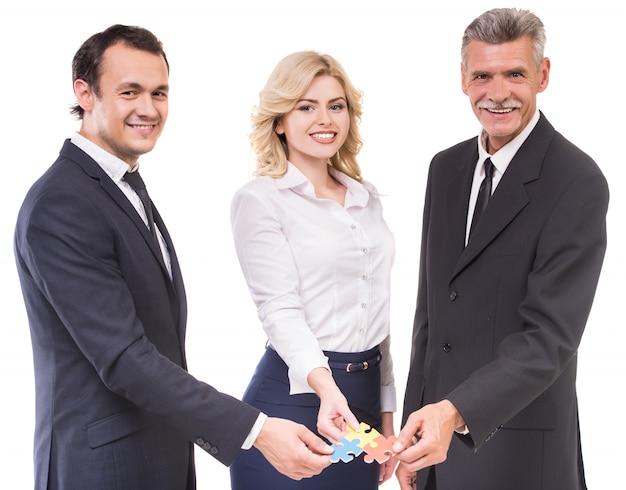 Geschäftsmänner und geschäftsfrau, die puzzlestücken sich anschließen. Premium Fotos