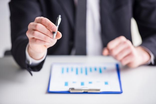 Geschäftsmann analysiert diagramme in seinem büro. Premium Fotos