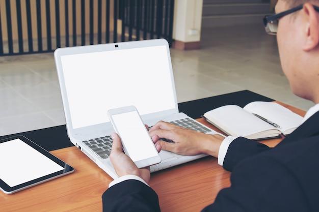 Geschäftsmann arbeitet an laptop und smartphone. Kostenlose Fotos
