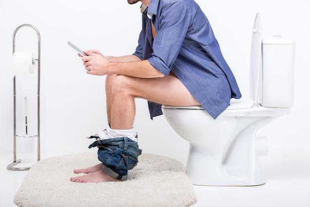 Geschäftsmann arbeitet mit tablette beim sitzen auf toilette. Premium Fotos