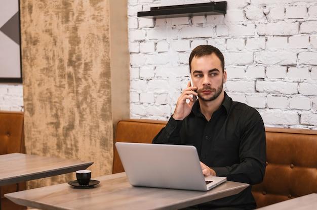 Geschäftsmann, der am handy im café spricht Premium Fotos